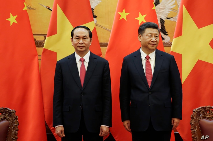FILE - Vietnamese President Tran Dai Quang, left, and his Chinese counterpart Xi Jinping attend a signing ceremony at the Great Hall of the People in Beijing.