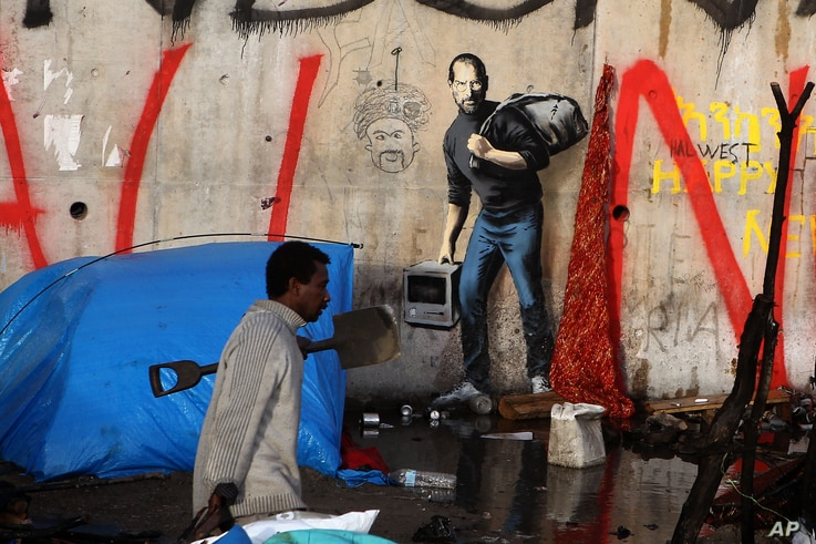 A migrant walks past a painting by English graffiti artist Banksy, at the entrance of the Calais refugee camp in France, in Calais, northern France, Monday, Dec. 21, 2015.