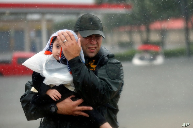 Sgt. Chad Watts of the Louisiana Department of Wildlife and Fisheries holds Madelyn Nguyen, 2, after he rescued her and her family by boat from floodwaters of Tropical Storm Harvey, in Houston, Aug. 28, 2017.