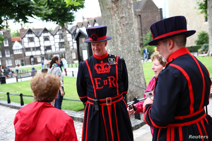 """Yeoman Warders interact with tourists at the Tower of London in London, July 20, 2017. """"When we are here looking after the general public, we're very much in the public domain, very, very busy answering lots of questions,"""" said John Donald, a Bee..."""
