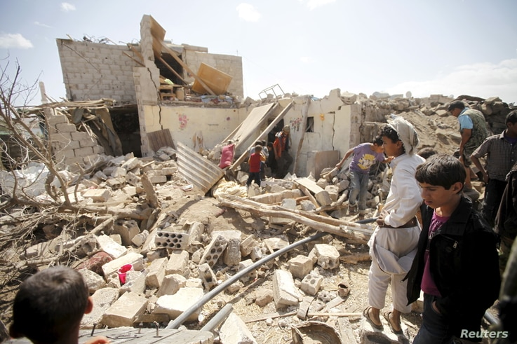 FILE - People inspect damage at a house after it was destroyed by a Saudi-led air strike in Yemen's capital Sana'a, Feb. 25, 2016.