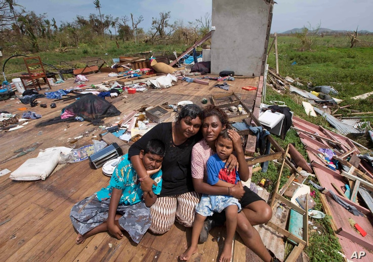 FILE - Sanjogeeta Kiran, right, with her sister Sulva Kiran, second left, and her children Shivendera, left, and Raajeen, sit amid the debris of their home in RakiRaki, Fiji, Feb. 24, 2016, after Cyclone Winston ripped through the island nation.