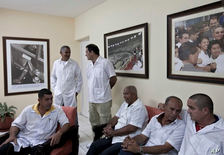 FILE - These Cuban doctors, waiting for the start of a press conference in Havana, were among 91 health workers who traveled to Liberia and Guinea to help with treatment of Ebola patients, Oct. 21, 2014.