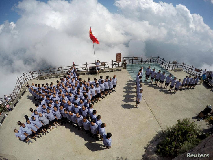 """Veterans of the Chinese People's Liberation army (PLA) navy stand in formation of a star and the Chinese characters """"August 1"""" on top of a mountain ahead of China's """"Army Day"""" in Luoyang, Henan province, July 31, 2016."""