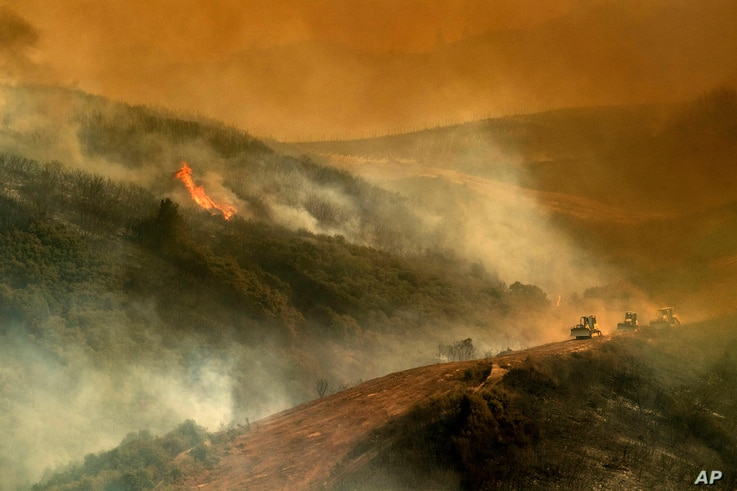 Bulldozer operators and their machines build containment lines while battling the River fire in Lakeport, Calif. The operators who steer heavy bulldozers across steep ridges face many dangers, from the flames themselves to unsteady dirt and rocky ter...