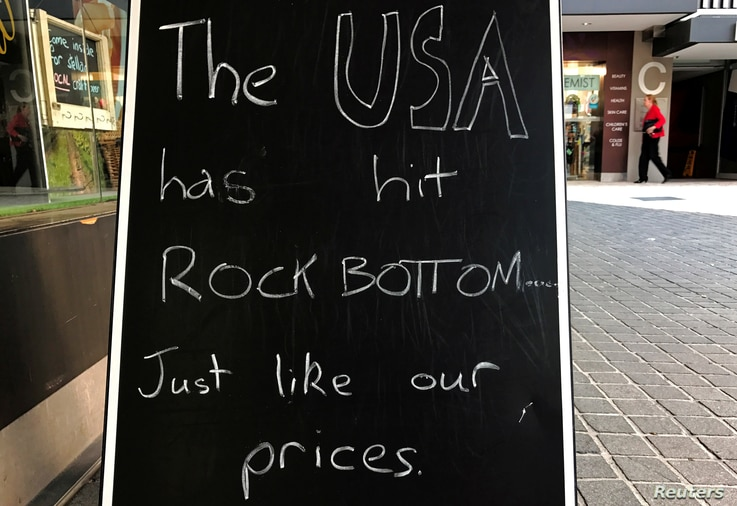 A shopper walks behind a sign on display outside a wine shop in Sydney, Australia Nov. 10, 2016 that comments on the recent U.S. election in which Republican candidate Donald Trump was victorious.