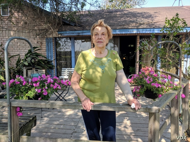 Pamela Taylor stands outside her ranch home in Brownsville, Texas, where she has lived for nearly 70 years. Following the 2006 Secure Fence Act, a barrier was built to her north, with an opening just big enough for two-lane traffic. (R. Taylor/VOA)