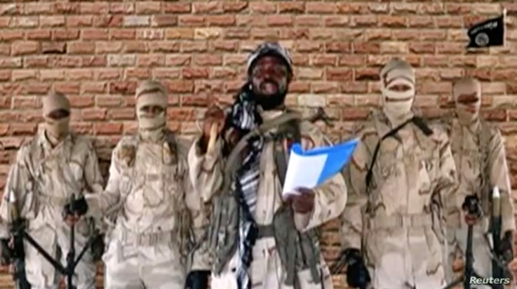 FILE - Leader of one of the Boko Haram group's factions, Abubakar Shekau speaks in front of guards in an unknown location in Nigeria in this still image taken from an undated video obtained on Jan. 15, 2018.