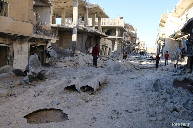 People inspect a damaged site after airstrikes on the rebel-held Sheikh Fares neighborhood of Aleppo, Syria, Oct. 1, 2016.