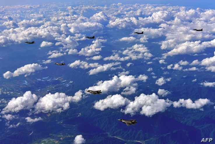 This handout photo taken on August 31, 2017 and provided by South Korean Defence Ministry in Seoul shows South Korean F-15K fighter jets and US F-35B stealth jet fighters flying over South Korea during a joint military drill aimed to counter North Ko