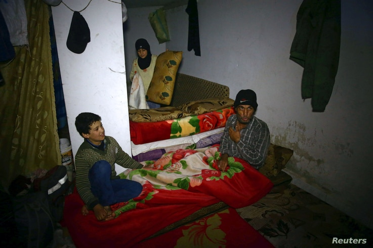 A man gestures as he sits in a shelter in the besieged town of Douma, eastern Ghouta, in Damascus, Syria, March 11, 2018.