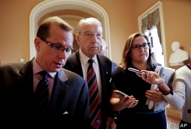 Sen. Chuck Grassley, R-Iowa, center, walks past members of the media as he heads to the Senate floor on Capitol Hill in Washington, Tuesday, Sept. 18, 2018.