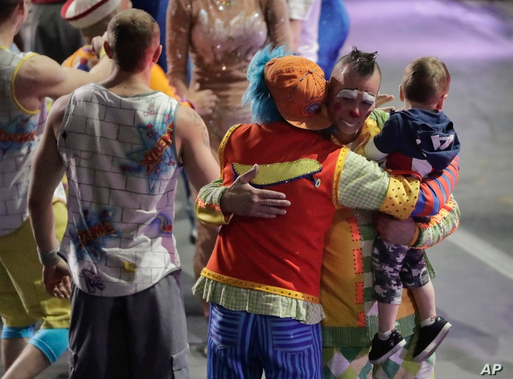 "Boss clown Sandor Eke hugs fellow clowns as he holds his 2-year-old son after the red unit's final performance, May 7, 2017, in Providence, R.I. ""The Greatest Show on Earth"" is about to put on its last show on earth."