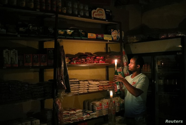 FILE - Mulugeta Desalegn, an owner of a convenience store, picks an item for a customer as he holds a candle, in Senaone, Soweto, South Africa, March 18, 2019.