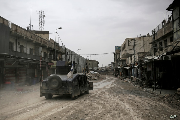 In this Tuesday, May 2, 2017 photo, a humvee of the Iraqi Federal Police drives through an abandoned street in western Mosul, Iraq.