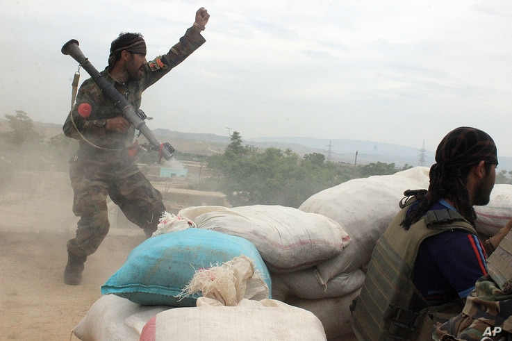 FILE - An Afghan National Army soldier (L) shouts at Taliban fighters, after firing a rocket towards Taliban positions, on the outskirts of Kunduz, northern Afghanistan, April 16, 2016.