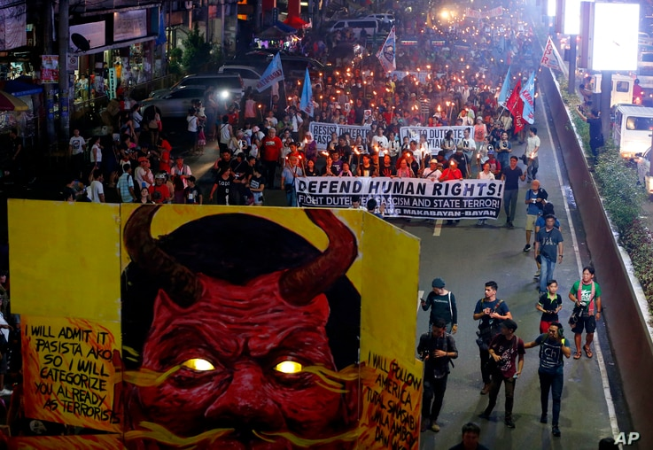 FILE - Protesters carry torches as they march toward the Presidential Palace in Manila to mark the U.N. Declaration of International Human Rights Day, Dec. 10, 2017, in Manila, Philippines.