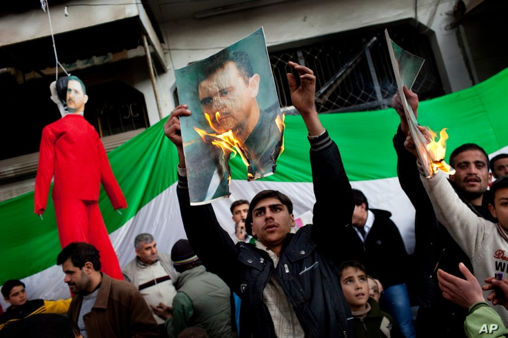 FILE - People burn portraits of Syrian President Bashar Al-Assad during a demonstration on the outskirts of Idlib, northern Syria, Feb. 26, 2012.