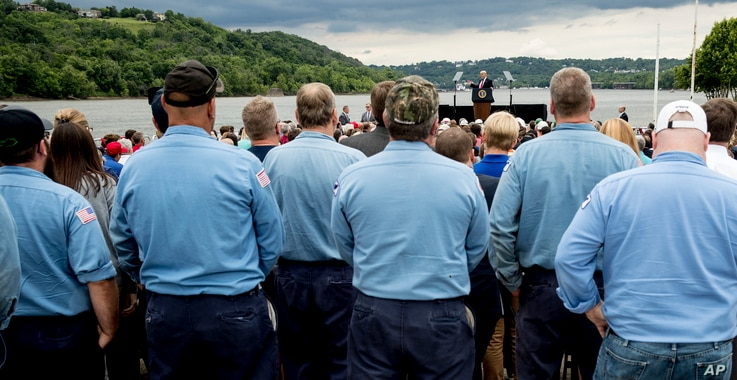 A coal barge is visible behind President Donald Trump as he speaks about infrastructure at Rivertowne Marina in Cincinnati, Ohio, June 7, 2017.