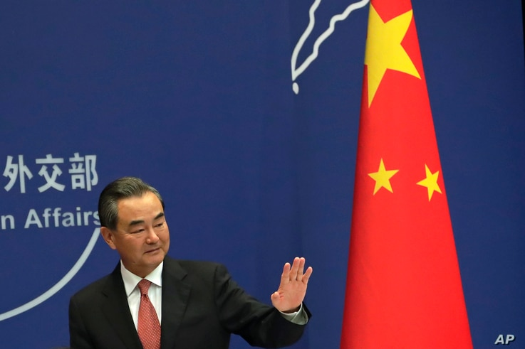 FILE - China's Foreign Minister Wang Yi waves after a press conference for the up-coming BRICS summit, at the Ministry of Foreign Affairs in Beijing, Aug. 30, 2017.