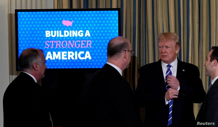 U.S. President Donald Trump speaks to attendees as he departs his infrastructure initiative meeting at the White House in Washington, U.S., Feb. 12, 2018.