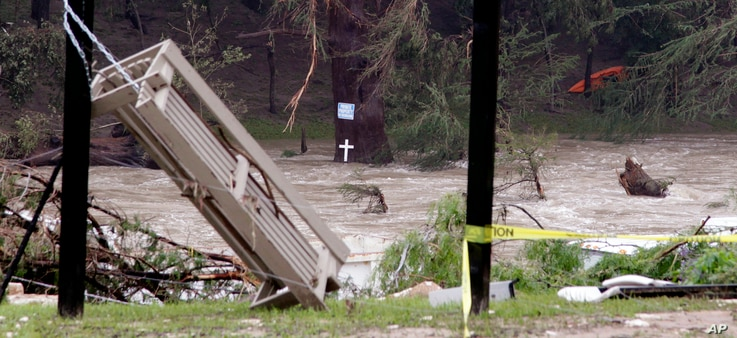 A cross sits at water-level of the still flooding Blanco River and in view of debris from a flood days earlier, Tuesday, May 26, 2015, in Wimberley, Texas.