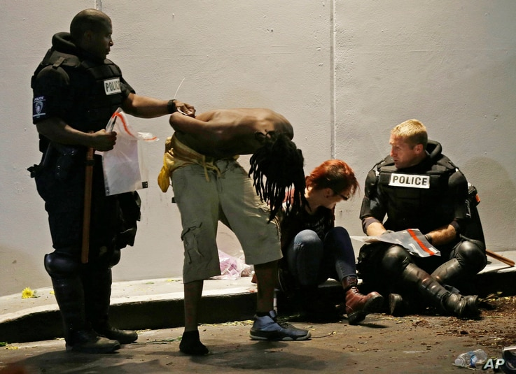 Police detain two people during protests in downtown following Tuesday's police shooting of Keith Lamont Scott in Charlotte, N.C., Wednesday, Sept. 21, 2016.