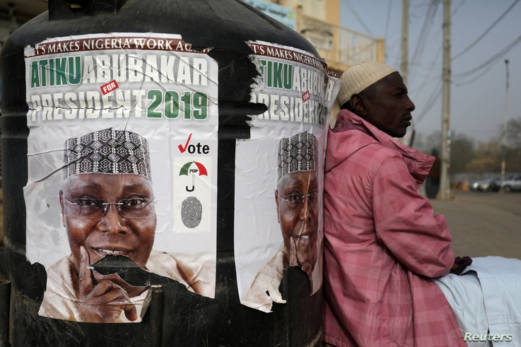 FILE PHOTO: A man sits next to a campaign poster of Atiku Abubakar, leader of the People's Democratic Party, days before the presidential election in Kano, Nigeria, Feb. 17, 2019.