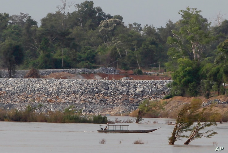 FILE - In this June 20, 2016 file photo, a fishing boat passes near a construction site of the Don Sahong dam, near Cambodia-Laos borders, in Preah Romkel village, Stung Treng province, northeast of Phnom Penh, Cambodia.