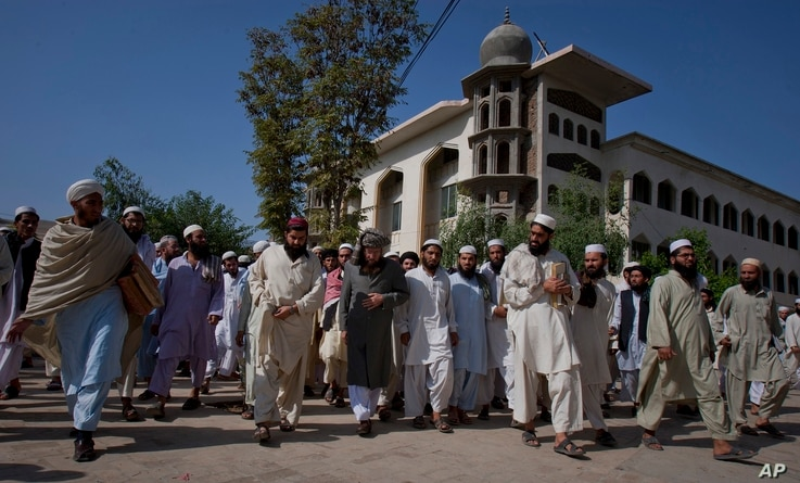 FILE-- Sami-ul-Haq, center in grey turban, a Pakistani Islamist politician and head of the Islamic seminary Darul Uloom Haqqania, is surrounded by students as he leaves after delivering a lecture at his seminary in Akora Khatak, Pakistan.