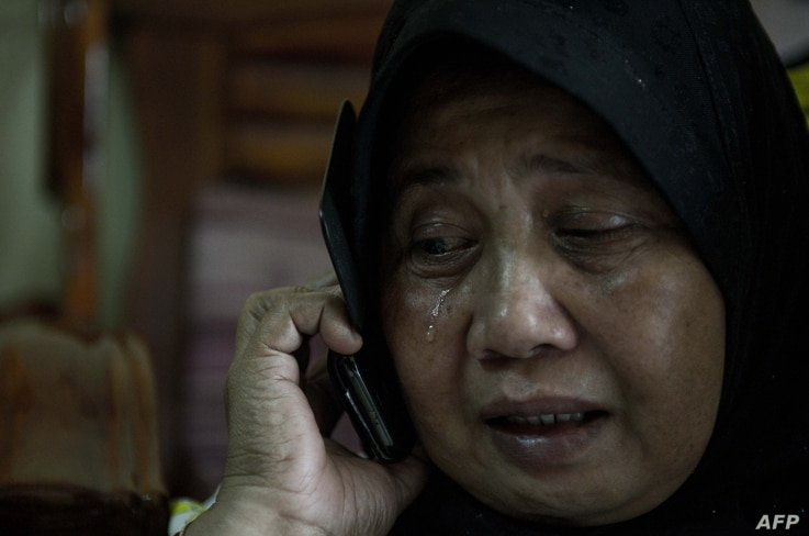 A relative of Norliakmar Hamid and Razahan Zamani, passengers on a missing Malaysia Airlines Boeing 777-200 plane, cries at their house in Kuala Lumpur on March 8, 2014.