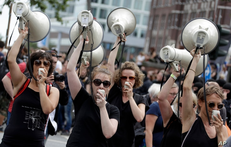 Women hold up megaphones during a protest against the G-20 summit in Hamburg, Germany, July 8, 2017.