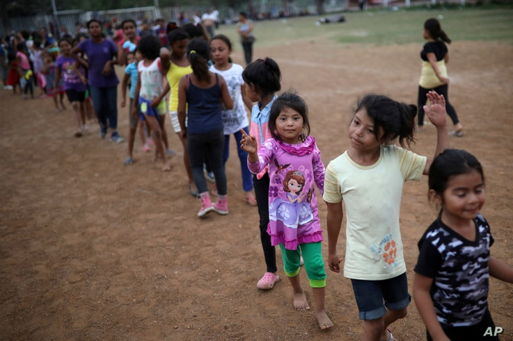 Children wait  to receive gifts after a show to entertain them at the sports club where Central American migrants traveling with the annual Stations of the Cross caravan have been camped out in Matias Romero, Mexico,  April 4, 2018.