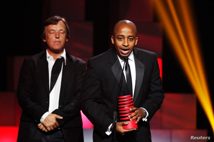 Co-founder of ushahidi.com, David Kobia (R), accepts a Special Achievement award during the 15th annual Webby Awards in New York, June 13, 2011.