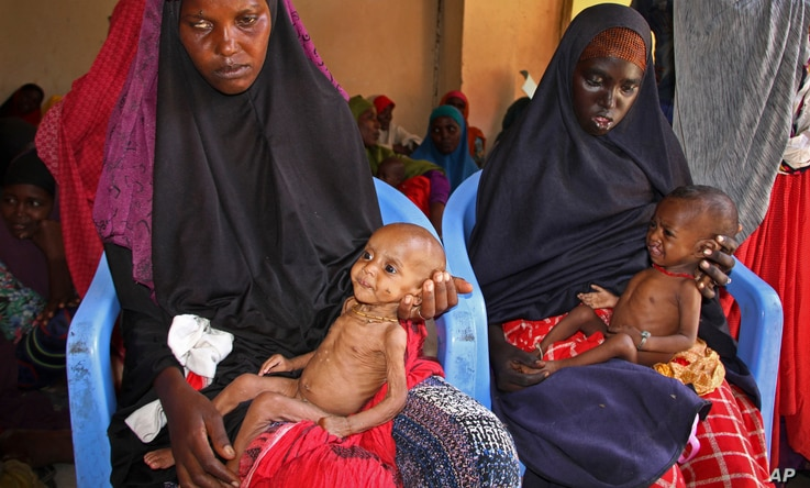 Malnourished babies are held by their mothers, both of whom fled the drought in southern Somalia, at a feeding center in a camp in Mogadishu, Somalia, Feb. 25, 2017.