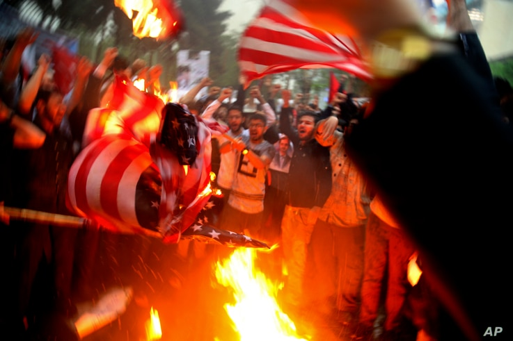 Iranian demonstrators burn representations of the U.S. flag during a protest in front of the former U.S. Embassy in response to President Donald Trump's decision Tuesday to pull out of the nuclear deal and reimpose sanctions, in Tehran, Iran, May 9, ...