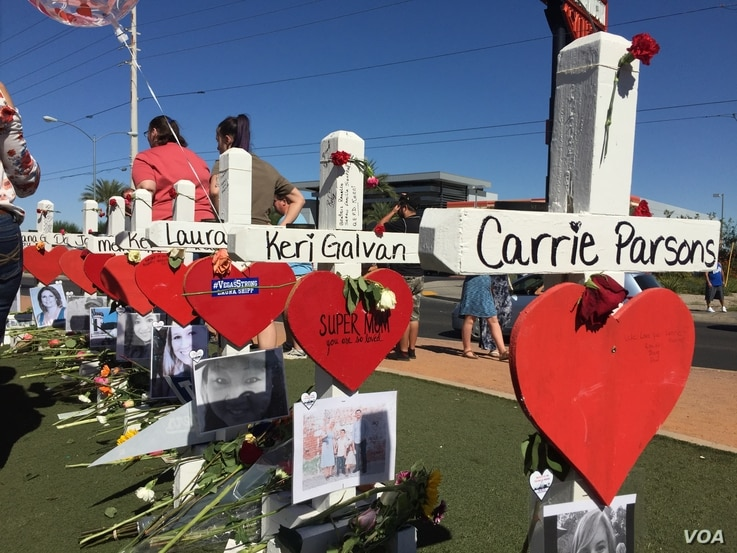 """The crosses, erected in a graceful, curvy line behind the """"Welcome to Las Vegas"""" sign, serve as markers of the lives of those who died when a gunman opened fire Oct. 1, 2017, at the crowd attending a country music concert in Las Vegas. Many visi..."""