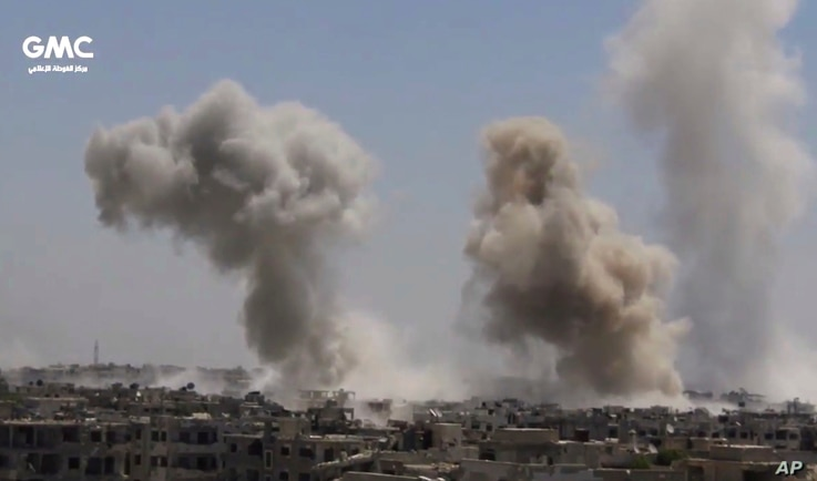 This frame grab from video provided on Aug. 13, 2017, shows smoke and debris rising after Syrian government ground-to-ground rocket strike on the Ain Terma, in the Eastern Ghouta suburb of Damascus.