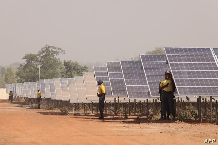People stand next to solar panels of the solar energy power plant in Zagtouli, near Ouagadougou, on Nov. 29, 2017, on its inauguration day.
