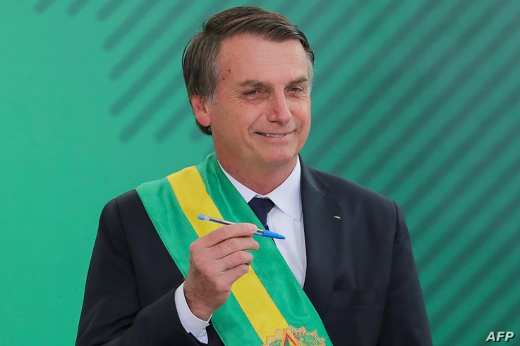 Brazil's new President Jair Bolsonaro poses with the pen used during the swearing-in ceremony for the minsters at the Planalto Palace in Brasilia, Jan. 1, 2019, after his own inauguration at the national Congress.