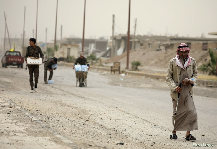 A civilian and fighters from the Syrian Democratic Forces (SDF) walk along a street in the Raqqa's al-Sana'a industrial neighborhood, Syria June 14, 2017. Mutual suspicion between Arabs and Kurds in Raqqa runs deep and predates the current conflict b...