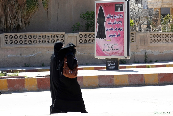 Veiled women walk past a billboard that carries a verse from Koran urging women to wear a hijab in the northern province of Raqqa, March 31, 2014.