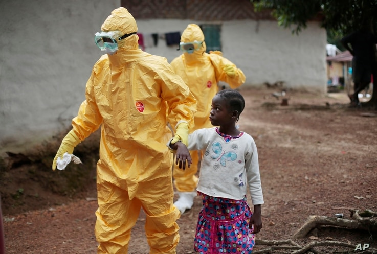 Health workers accompany a nine-year-old who contracted the Ebola virus to a Monrovia treatment center on Sept. 30, 2014.