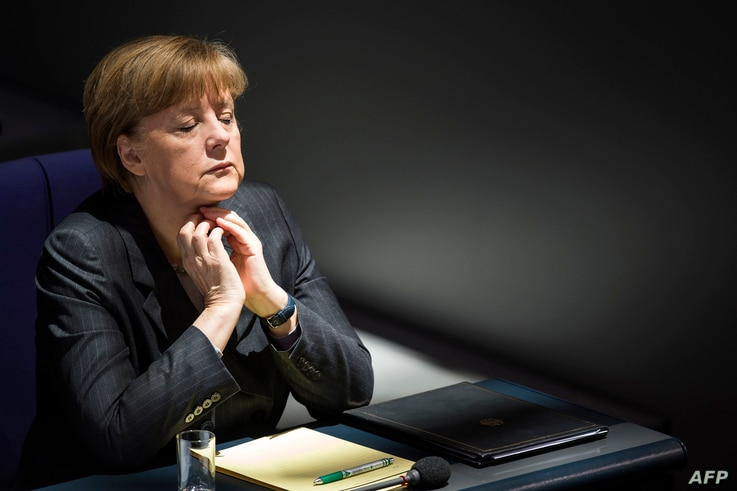 German Chancellor Angela Merkel listens to Gregor Gyisi of the Left party answer her speech on the government's policy on Ukraine at the Bundestag, Germany's lower house of parliament in Berlin on March 13, 2014.