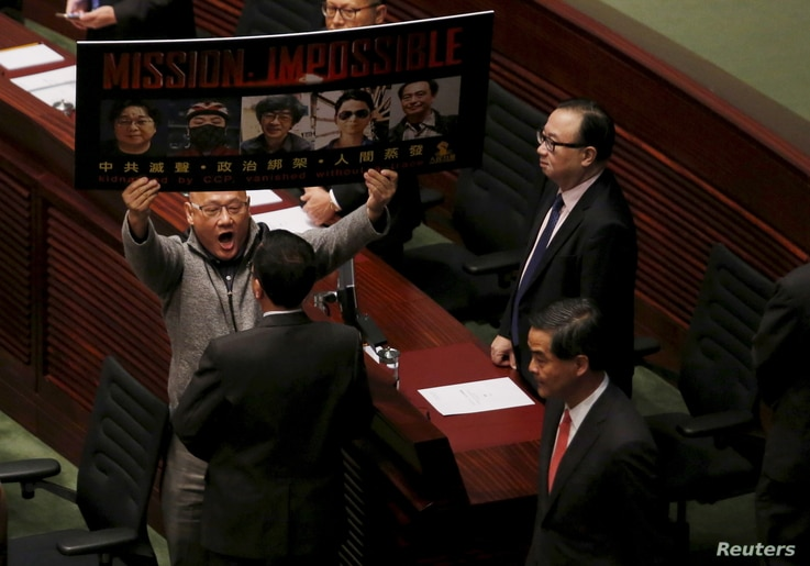 FILE - Pro-democracy lawmaker Albert Chan, carrying portraits of five missing booksellers from a local bookstore, shouts to Hong Kong Chief Executive Leung Chun-ying as he enters the Legislative Council chamber in Hong Kong, China, Jan. 13, 2016.