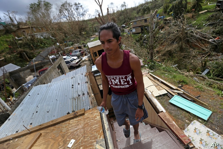 Jose Colon walks up the stairs of his friend's destroyed home, in the aftermath of Hurricane Maria, in Aibonito, Puerto Rico,  Sept. 25, 2017.