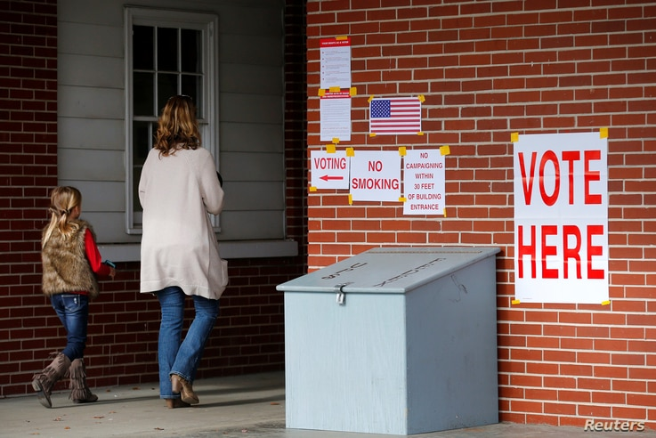 Anna Atkinson walks into a polling station with her 8-year-old daughter Tori, in Gallant, Alabama, Dec. 12, 2017.