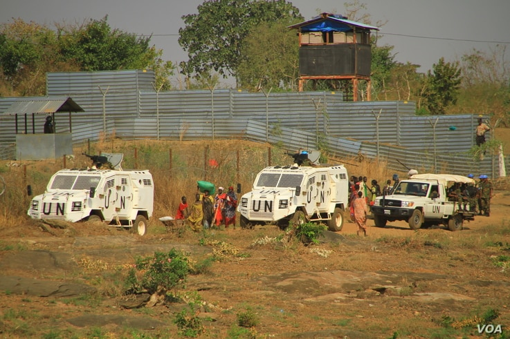 Internally displaced people walk next to U.N. vehicles on the perimeter of a protection of civilians (POC) site in Juba, South Sudan, Dec. 5, 2016. (J. Craig/VOA)