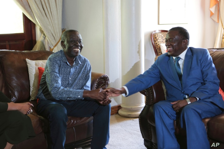 Zimbabwean President Emmerson Mnangagwa, right, talks to Morgan Tsvangirai, the main opposition leader in Zimbabwe, during a visit to his residence in Harare, Jan. 5, 2018.