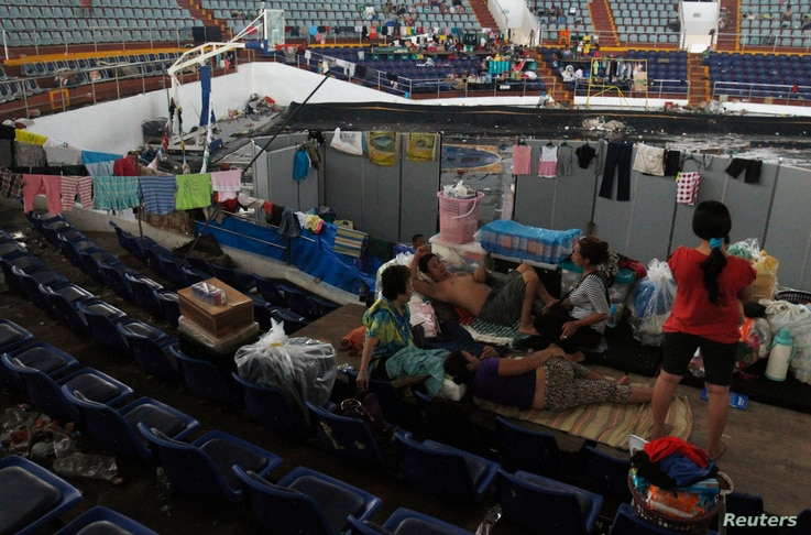 Families take refuge in an indoor basketball stadium at the Tacloban City Convention Center, which has become a homeless shelter after the super typhoon Haiyan battered the area, Nov. 12, 2013.